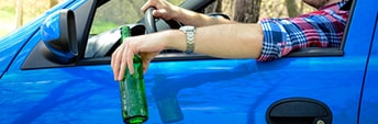 A young man drinking a beer while driving a car